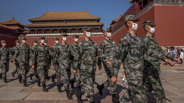 Chinese paramilitary police officers wearing protective face masks march past the entrance to the Forbidden City on National Day, in Beijing, China, 01 October 2021.