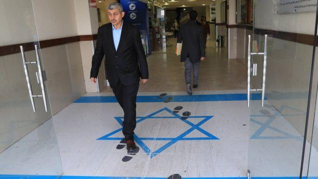 رجل يمشي فوق رسم للعلم الإسرائيلي
