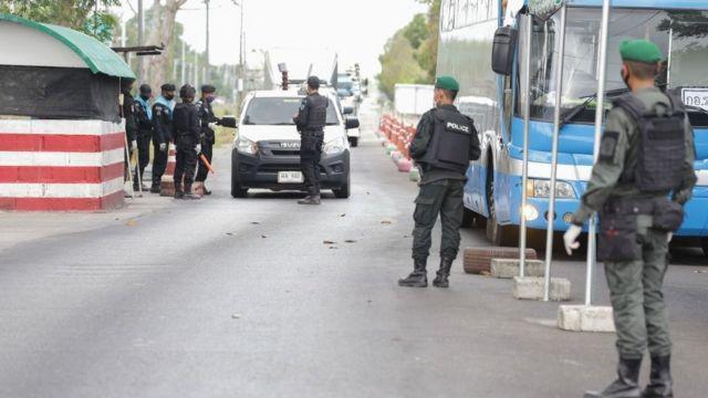 Cảnh sát và các quan chức bao quanh một chiếc xe hơi tại một trạm kiểm soát được thiết lập để ngăn chặn sự lây lan của virus corona COVID-19 ở quận Nongchik, trên biên giới của tỉnh Pattani phía nam Thái Lan vào ngày 26/3/2020