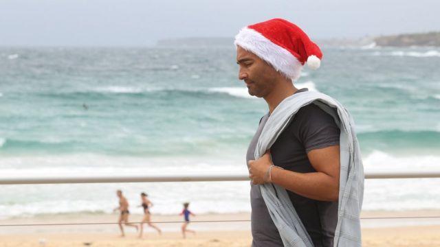 مردی با کلاه سنتا در یکی از سواحل نزدیک به سیدنی در استرالیا. در نیمکره غربی حالا تابستان است و هوا مناسب تفریحات آبی