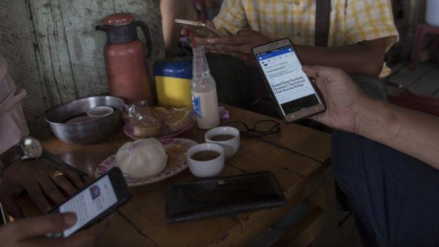 Customers in a cafe in Myanmar using Facebook