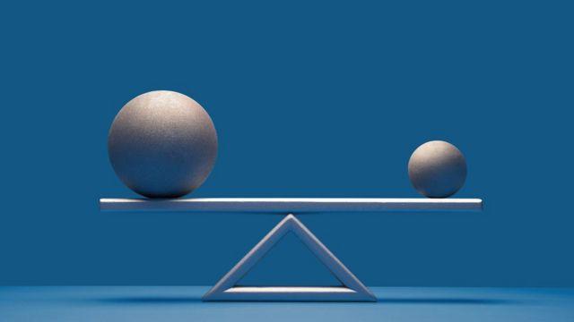 Balança com material metálico, com uma bola maior do que a outra em cada lado