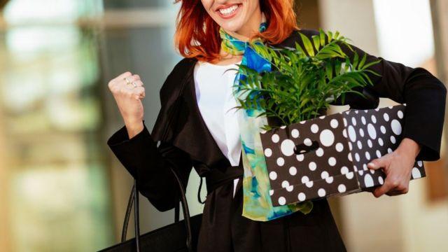 Una mujer con una caja que contiene pertenencias del trabajo.