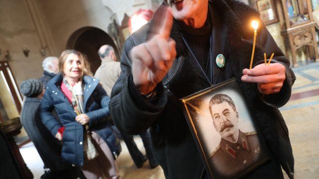 Мужчина со свечкой и портретом Сталина