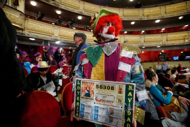 Un hombre disfrazado de payaso con fotocopias de su billete.