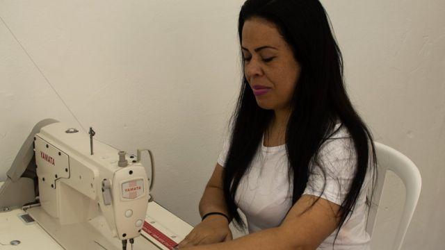 Flavia Maria da Silva costurando em máquina