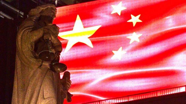 香港终审法院大楼楼顶正义女神像映照在一面投射在LED屏幕的中国国旗下(30/9/2019)