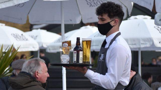 Camarero enmascarado con bandeja de bebidas en restaurante.