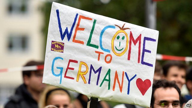 """People welcome refugees with a banner reading """"welcome to Germany"""" in Dortmund, Germany, Sunday, Sept. 6, 2015"""