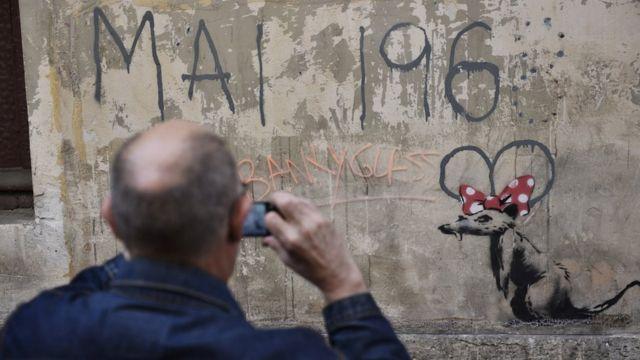 "Čovek fotografiše mural za koji se veruje da je Benksijev, na kojem se vidi pacov sa mašnom Mini Maus i natpisom ""Maj 1968."""