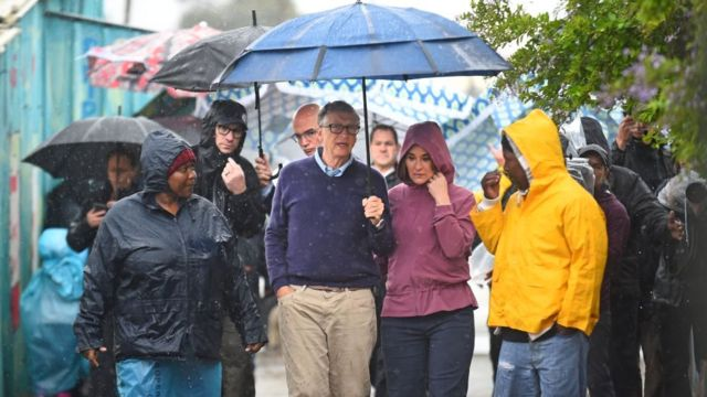 Bill and Melinda Gates brace the rain as they visit the township of Khayelitsha on October 25, 2019 in Cape Town, South Africa