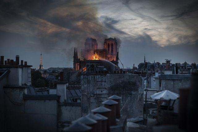 Flames and smoke are seen billowing from Notre-Dame's roof