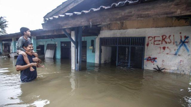 Warga melintas di depan rumah yang terendam banjir di kawasan Cilangkap, Jakarta Timur, Selasa (25/02).
