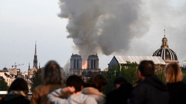 People watch the landmark Notre-Dame Cathedral burning in central Paris on April 15, 2019