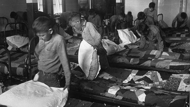 Em foto em preto e branco, crianças arrumam camas em abrigo