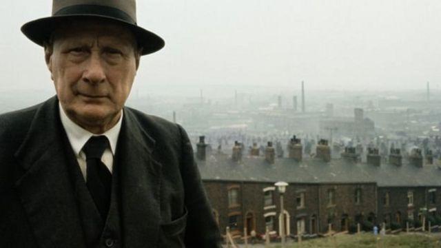 LS Lowry di dekat rumahnya di Pendlebury, Lancashire, pada tahun 1964, dengan pabrik di belakangnya.