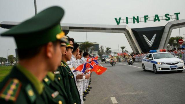 Cảnh sát Việt Nam đứng bên cạnh các sinh viên vẫy cờ Việt Nam và Triều Tiên khi đoàn xe chở đoàn Triều Tiên rời nhà máy của Vinfast tại Hải Phòng vào ngày 27/2/2019.