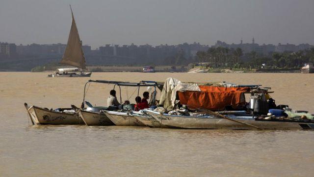 صيادو سمك في نهر النيل قرب القاهرة. يقول مسؤولون إن المياه القاتمة المليئة بالطمي ادت الى اغلاق عدة محطات تصفية في البلاد مما ادى الى انقطاع المياه في عدة مناطق