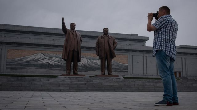 Kuzey Kore'nin eski liderlerinin heykellerini fotoğraflayan bir turist
