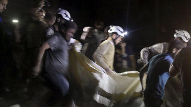 アレッポ空爆で負傷した人を運ぶ「ホワイト・ヘルメッツ」のメンバーら(27日)