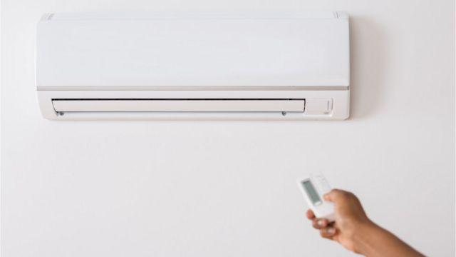 Braço aponta controle remoto para aparelho de ar condicionado
