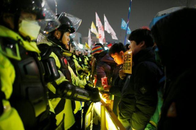 متظاهرون يقفون أمام الشرطة