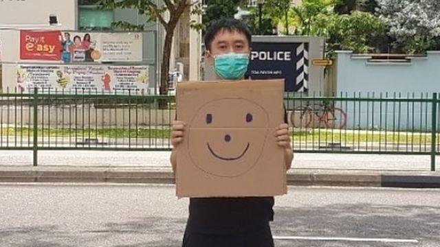 范国瀚在新加坡大巴窑邻里警局外举起画上笑脸的纸皮(范国瀚提供照片28/3/2020)