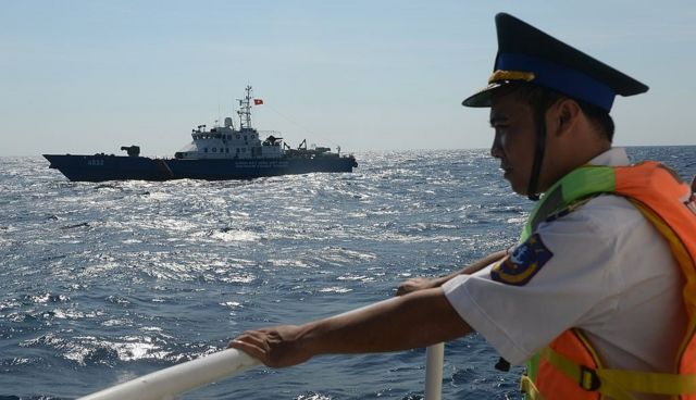 Một cảnh sát biển Việt Nam đăm đăm nhìn tàu hải cảnh Việt Nam di chuyển gần dàn khoan của Trung Quốc tháng Năm, 2014.