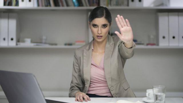 """Una mujer ejecutiva señala """"alto"""" con la mano"""