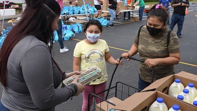 Florida'da yiyecek yardımı alan bir kadın ve çocuğu.