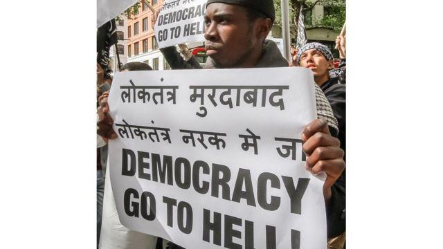 """Brusthom Ziamani con un cartel que reza: """"que la democracia se vaya al infierno"""""""