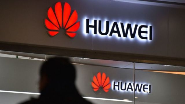 Un hombre caminando solo cerca de una tienda de Huawei.
