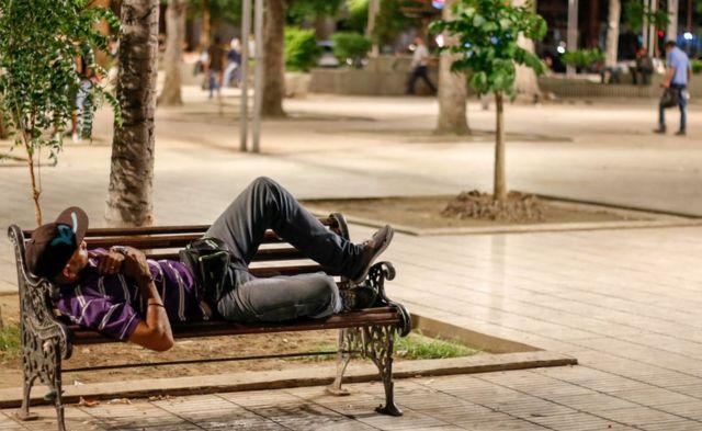 Un hombre duerme en un banco tras cruzar el Puente Internacional Simón Bolívar.