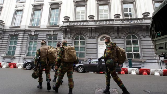 Belgian soldiers walk the streets after counter-terror raids.