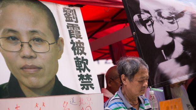 A man observes a minute of silence between photos of late Chinese dissident and Nobel Price recipient Liu Xiaobo (R) and his wife Liu Xia (L) in a booth set up by supporters in Hong Kong, China, 10 July 2018.