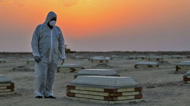 A masked grave digger observers the graves in a cemetery in Iraq