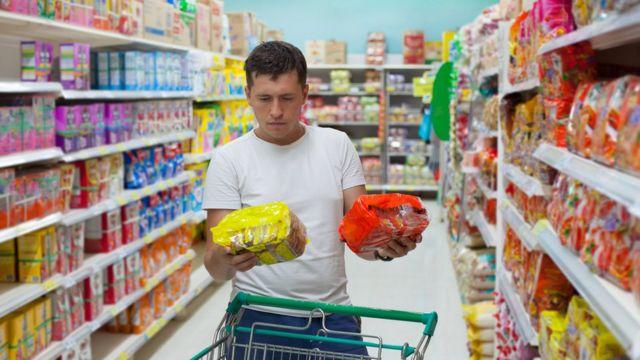 Homem escolhendo produtos em supermercado
