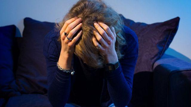 امرأة تضع يديها على رأسها بسبب التفكير الشديد والقلق