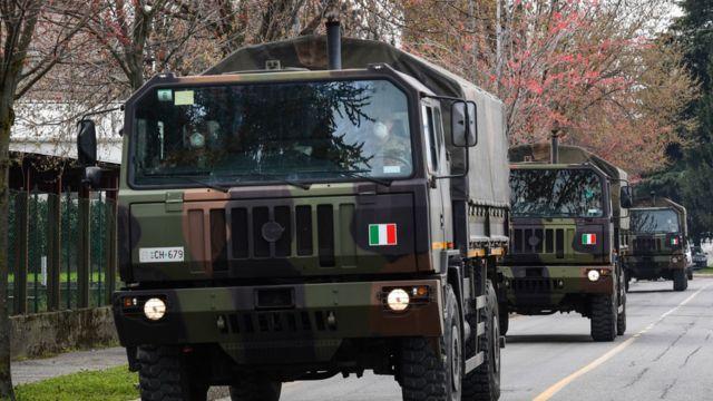 Caminhões do exército italiano em comboio pelas ruas de Bergamo, na Itália