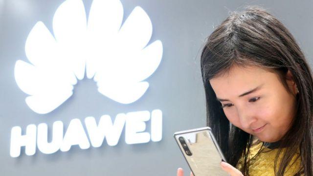 Una mujer joven mirando un teléfono inteligente Huawei.