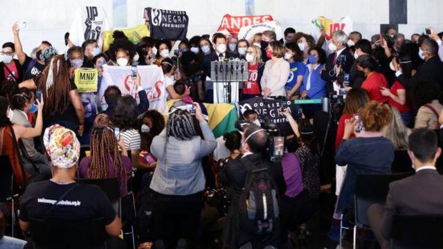 Dezenas de pessoas reunidas em volta de palanque, segurando bandeiras diversas de movimentos sociais, entre outros