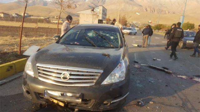 Foto do carro do cientista após o ataque, com os vidros rachados e danos causados por aparente explosão