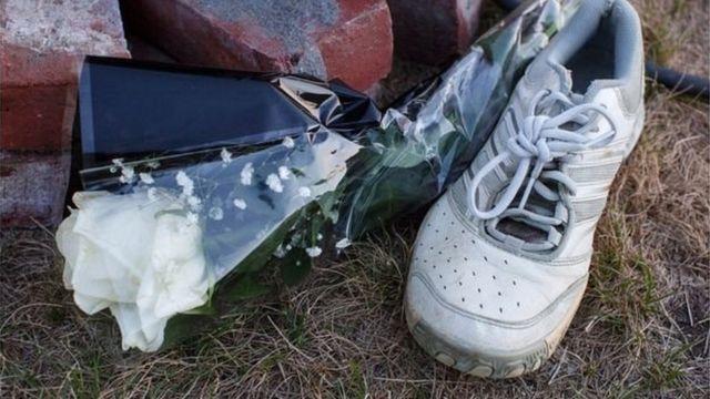 یک لنگه کفش مخصوص دویدن و یک دسته گل در مراسم یادبود ونسا مارکوتا، زنی که سال ۲۰۱۶ وقتی برای دویدن بیرون رفته بود، به قتل رسید