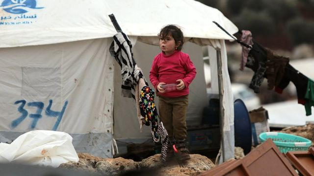 A Syrian girl walks past a tent at a makeshift displacement camp in Idlib province, Syria (18 February 2020)