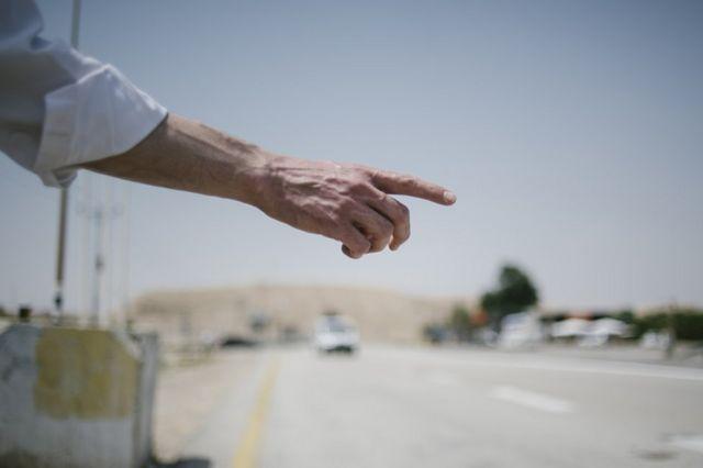 رجل يستوقف سيارة مقبلة