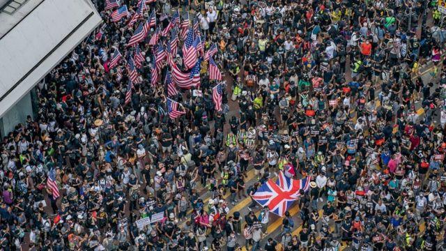 舉著美國國旗和英國國旗的香港示威者