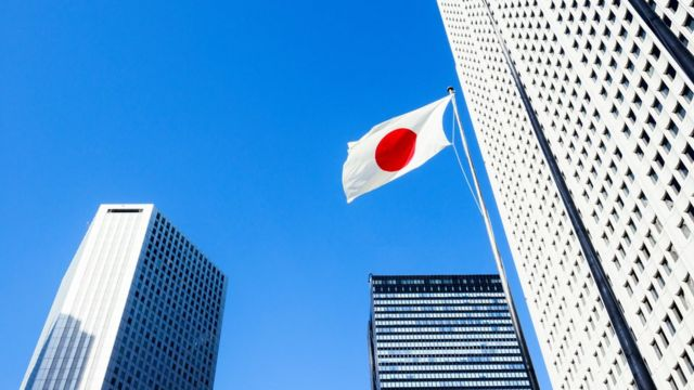Building in Tokyo and flag of Japan