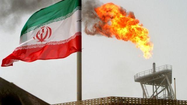 Una bandera de Irán junto a instalaciones energéticas