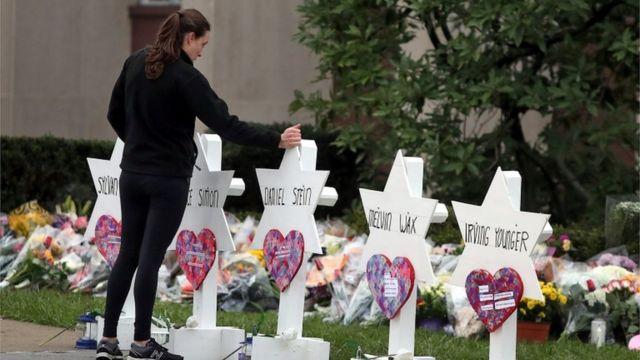 """在匹兹堡的""""生命之树""""犹太教堂外,一名妇女站在哀悼枪击事件遇害者的鲜花和悼念物品前。"""