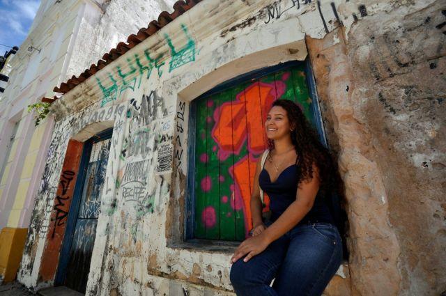 Fernanda Silmara Silva dos Santos sentada em frente a uma casa em Natal